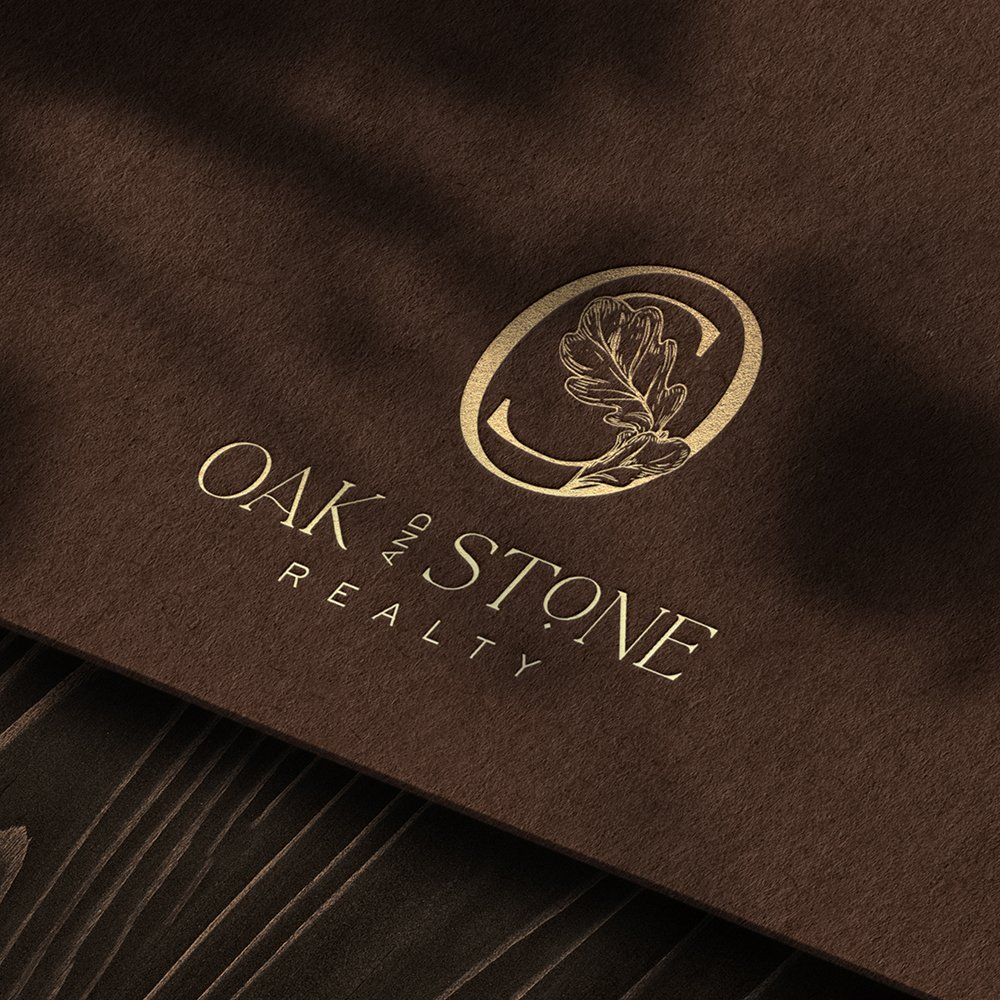 luxurious, professional logo design for Oak and Stone Realty, rendered in rich brown and gold foil